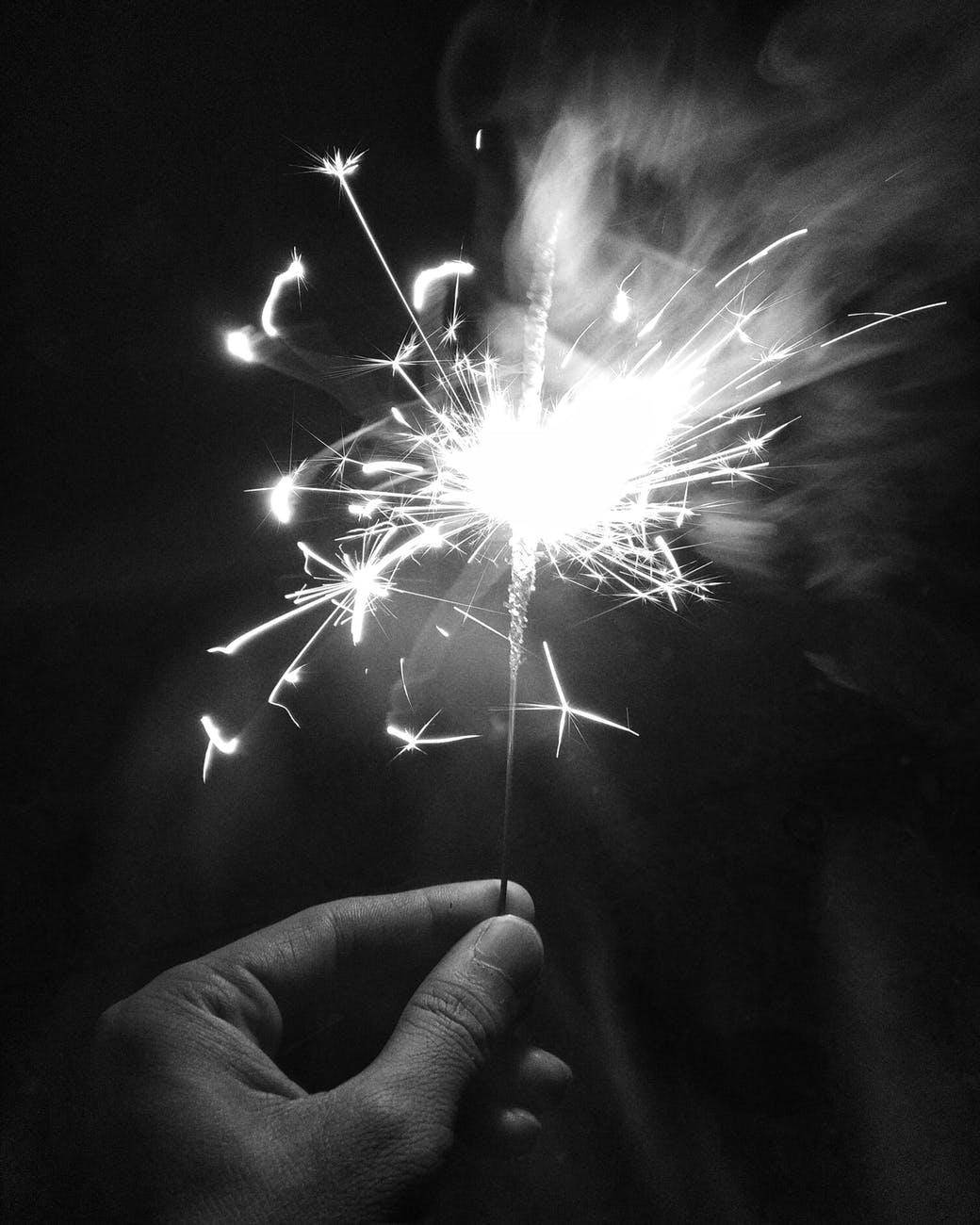 monochrome photo of person holding sparkler